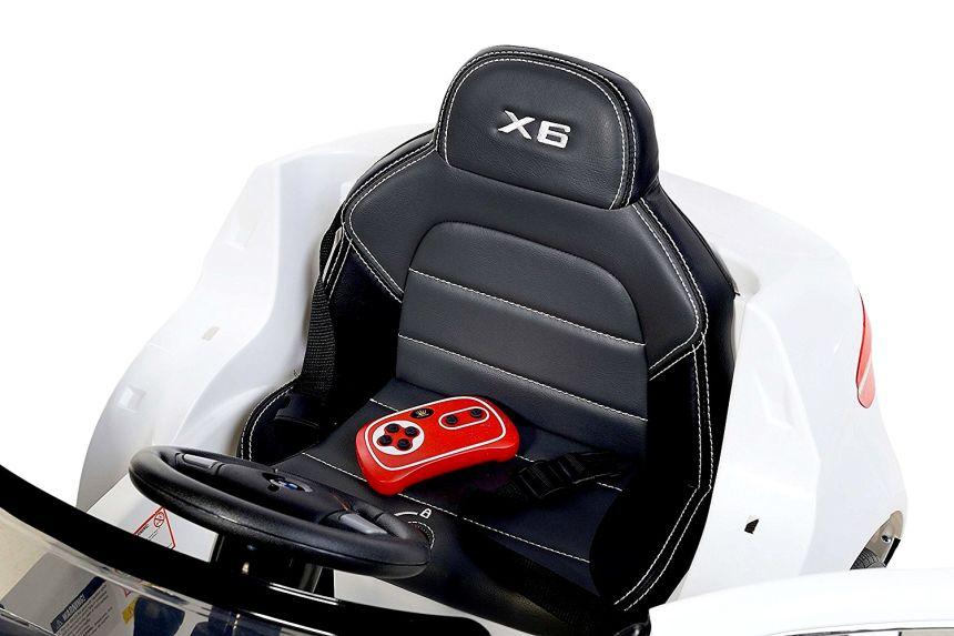 Il comodissimo sedile in pelle marchiato X6 della BMW elettrica Lamas Toys, completo di cinture di sicurezza, e con in bella vista il telecomando parentale